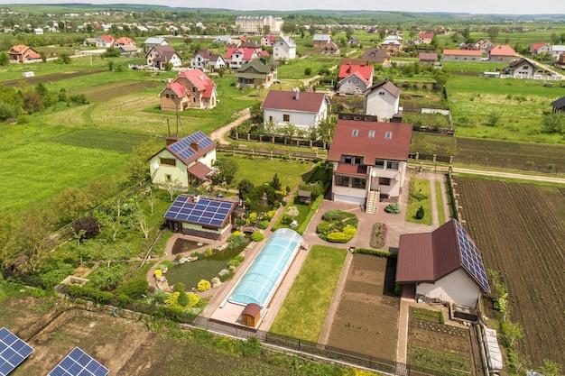 Вид с воздуха на частный дом летом с синими солнечными фотоэлектрическими панелями на крыше и во дворе.
