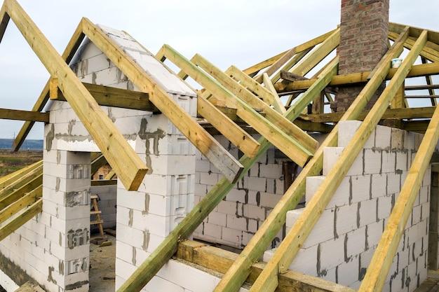 Вид с воздуха на частный дом со стенами из газобетона и деревянным каркасом будущей крыши.