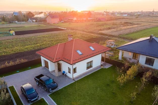 Вид с воздуха на частный загородный дом с припаркованными автомобилями на заднем дворе.