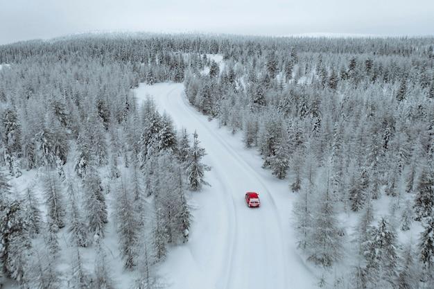 Вид с воздуха на красный автомобиль, проезжающий через заснеженный лес в лапландии, финляндия