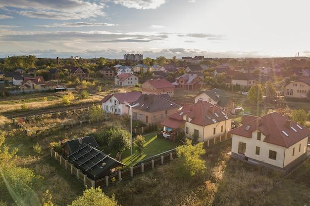 Вид с воздуха на жилой частный дом с солнечными батареями на крыше и турбиной ветрогенератора