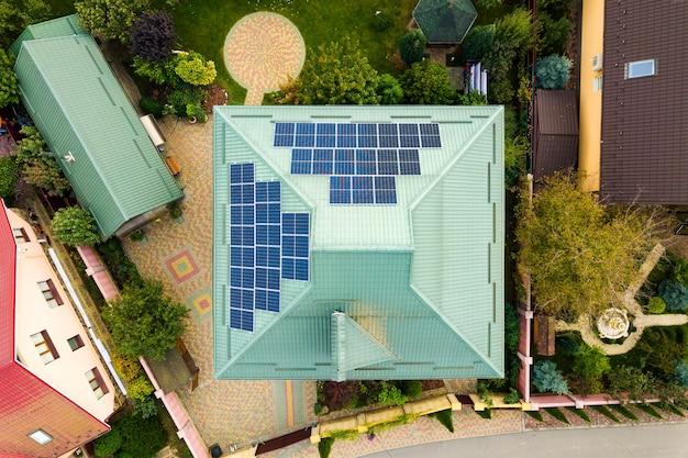 주거 지역 개념의 지붕에 깨끗한 전기를 생산하기위한 태양 광 태양 광 패널이있는 시골 개인 주택의 공중보기