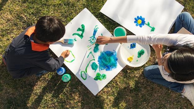 작은 소년과 젊은 여성이 작업복을 입고 흰색 표면에 붓과 붓으로 그림을 그리고 배경에 옷이 놓여 있는 화창한 날 안뜰에서 공중 전망.