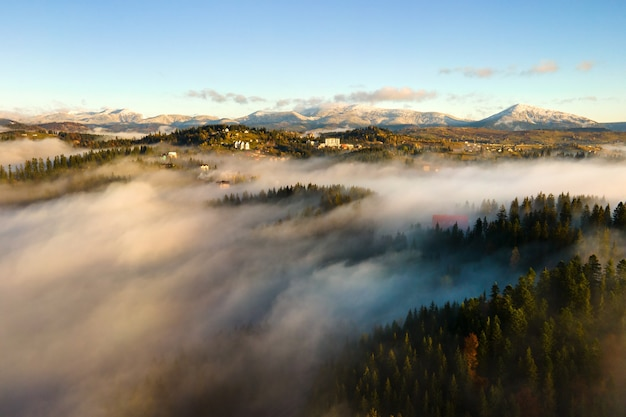 Аэрофотоснимок небольшой далекой деревни домов на вершине холма осенью туманные горы на восходе солнца.