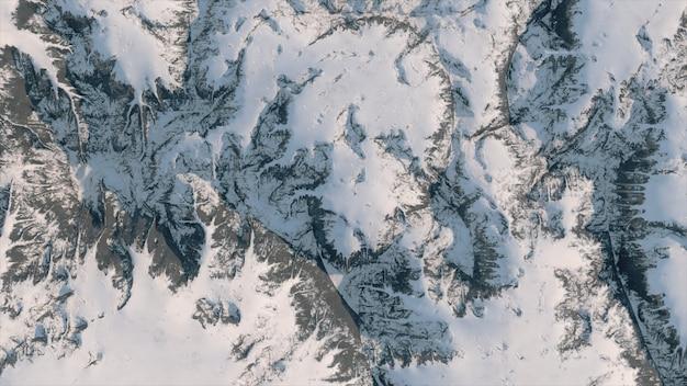 曲がりくねった道と雪に覆われた山脈の空撮。