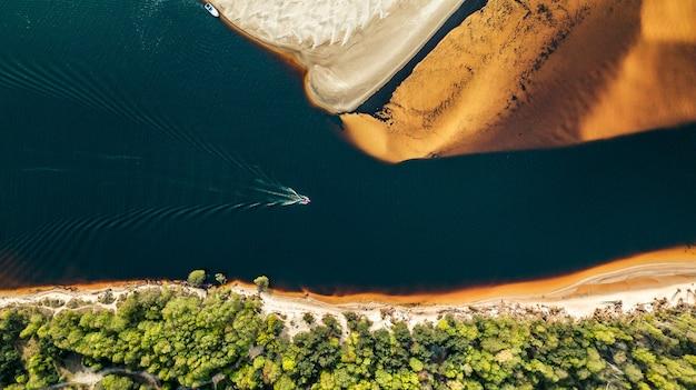 Вид с воздуха на катер, плывущий по реке на берегу золотого песка