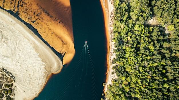 金色の砂の岸にある川に沿って航行するスピードボートの航空写真