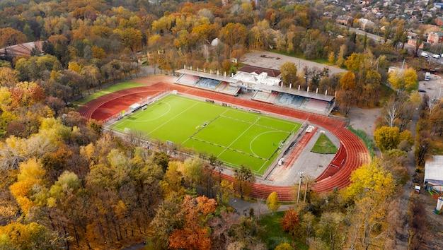 Вид с воздуха на спортивный стадион в городе, окруженном осенними деревьями.