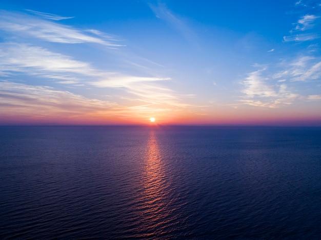 夕焼け空の空撮。海の上の夕方の空の雲と空中劇的な金の夕焼け空。