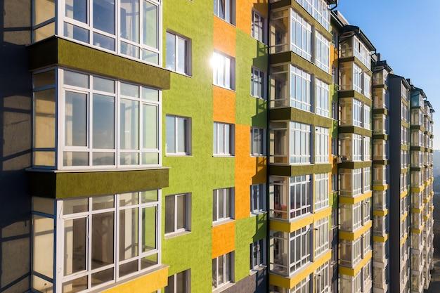 많은 창문과 발코니가있는 고층 주거용 아파트 건물의 조감도.
