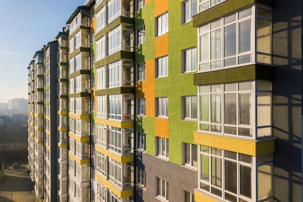많은 창과 발코니와 키 큰 주거 아파트 건물의 공중 전망.