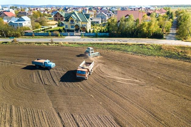 秋に収穫した後、黒い農業畑を耕すトラクターの航空写真。
