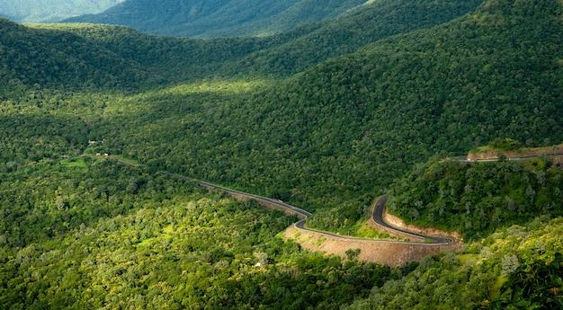 風光明媚な緑の山々の曲がりくねった道の空撮