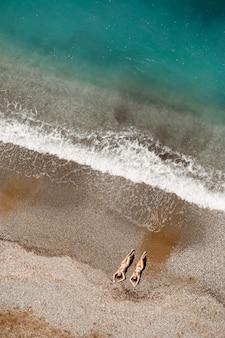 Вид с воздуха на женщину в средиземном море в турции. красивый летний пейзаж с девушкой, чистой лазурной водой, волнами и песчаным пляжем в солнечный день. вид сверху с летающего дрона.