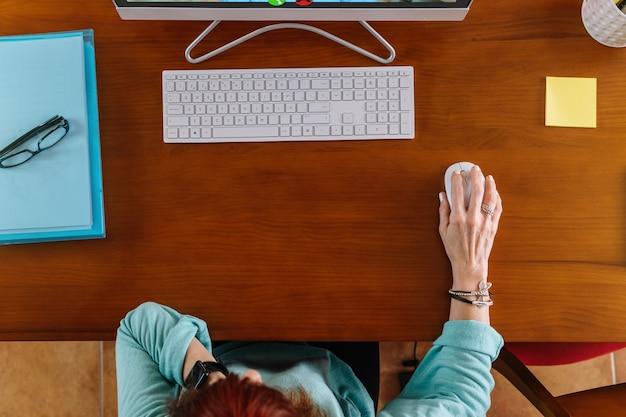 Вид с воздуха на женщину, использующую мышь компьютера во время удаленной работы за столом дома