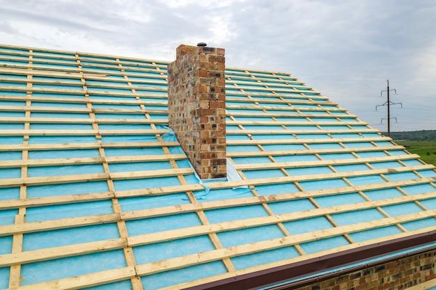 건설중인 벽돌 집의 나무 지붕 프레임의 공중 전망.