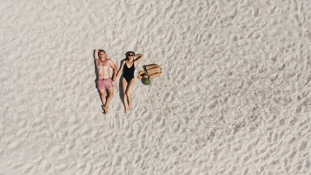 白い砂浜に横たわっている若いカップルの空撮。水着姿の男女が一緒に時間を過ごす