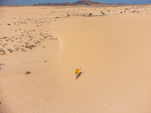 카나리아 제도 푸에르테벤투라 코랄레호 공원의 모래 언덕에서 드론을 날리는 청년의 공중 전망. 스페인