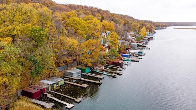 ボートの通路がある川のほとりにある村の秋の風景の空撮