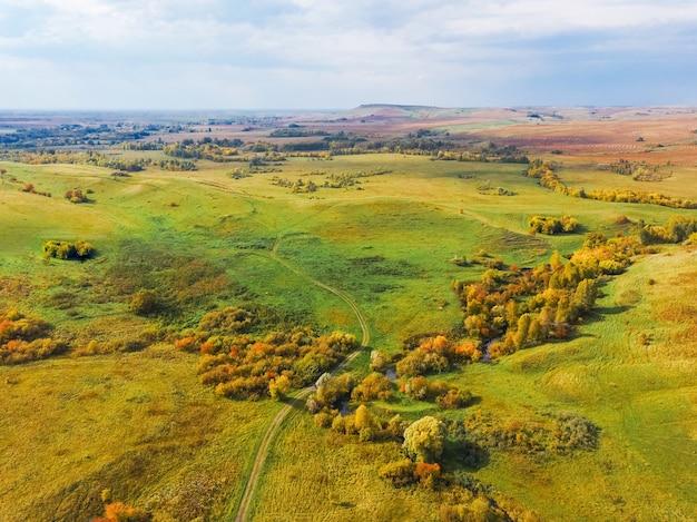 Вид с воздуха на осенний пейзаж с холмами и желтыми деревьями