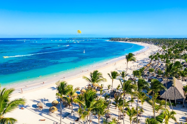 도미니카 공화국의 바바로 해변 푼타 카나 열대 리조트의 공중 전망. 야자수, 우산, 패러세일링 풍선이 있는 아름다운 대서양 열대 해변.