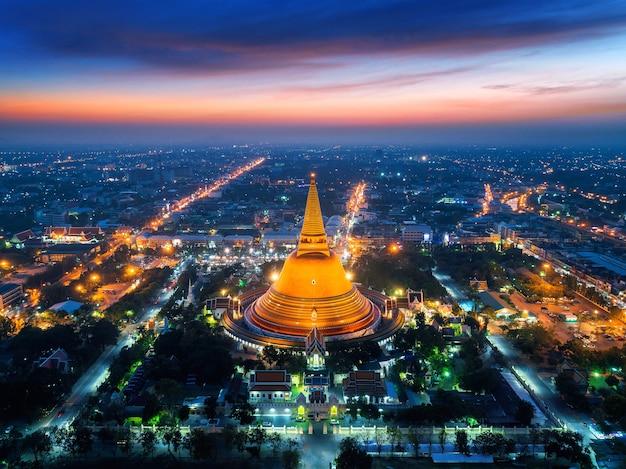 Вид с воздуха на красивую пагоду глоден на закате. храм пхра патом чеди в провинции накхон патом, таиланд.