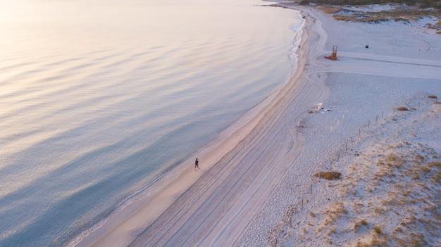 見張り塔のある砂浜の海岸に沿って歩く観光客と美しい海の景色の空撮。のどかな海と展望台のある砂浜。