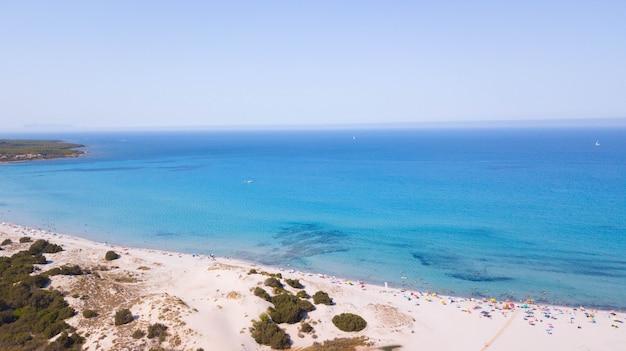 澄んだ空を背景に砂浜の海岸で観光客と美しい海の景色の空撮。観光客、ビーチの地平線と澄んだ空と夏の海の風景
