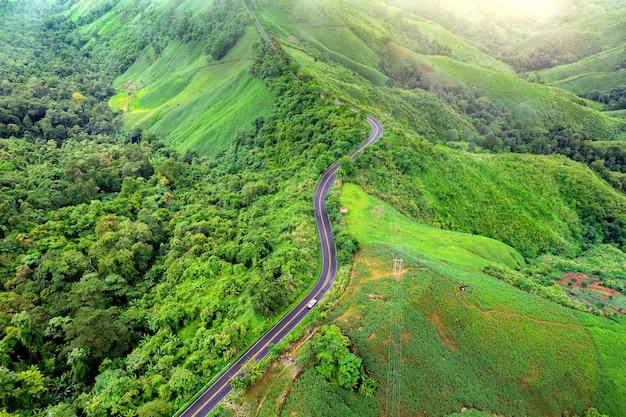 タイ、ナン州の緑のジャングルと山の頂上に美しい空の道の空撮