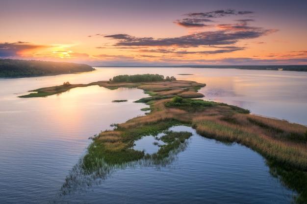 여름에 해질 때 강가에 푸른 나무와 풀이 있는 아름다운 작은 섬의 공중 전망. 섬, 초원, 푸른 물에 주황색 하늘 반사가 있는 다채로운 풍경. 평면도. 자연