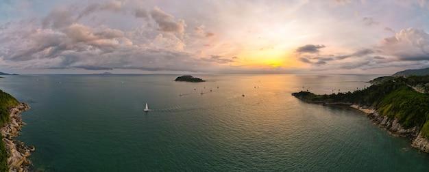 ターコイズブルーの海に沈む美しい夕日の空撮