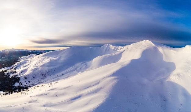 Вид с воздуха на красивые зимние горные склоны, покрытые снегом и еловым лесом в солнечный безоблачный день. европейское понятие красоты горнолыжного курорта. место для текста