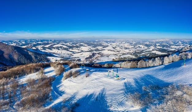 晴れた雲ひとつない日に雪とモミの森に覆われた美しい冬の山の斜面の空撮。ヨーロッパのスキーリゾートの美しさの概念