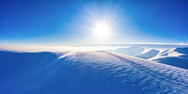 Вид с воздуха на красивые зимние горные склоны, покрытые снегом и еловым лесом в солнечный безоблачный день. европейское понятие красоты горнолыжного курорта