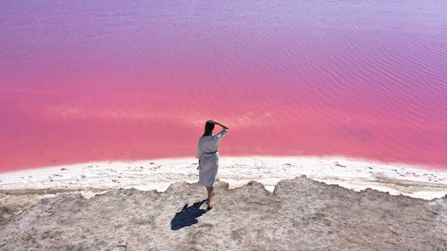 Вид с воздуха на красивую молодую женщину в белом платье, идущую по удивительному розовому озеру с морской водой и голубым небом. одесса, украина.