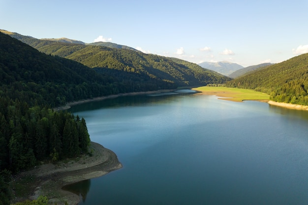 Вид с воздуха на большое озеро с чистой голубой водой между высокими горными холмами, покрытыми густым вечнозеленым лесом.
