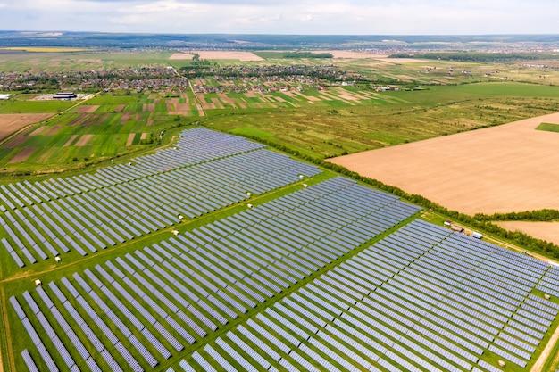 Вид с воздуха на большую устойчивую электростанцию с множеством рядов солнечных фотоэлектрических панелей для производства экологически чистой электроэнергии. возобновляемая электроэнергия с нулевым выбросом вредных веществ.