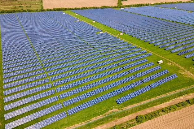 Вид с воздуха на большую устойчивую электростанцию с множеством рядов солнечных фотоэлектрических панелей для производства экологически чистой электроэнергии. возобновляемая электроэнергия с концепцией нулевого выброса.