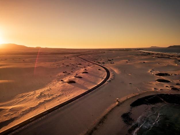 砂漠とビーチの真ん中にある黒いアスファルト道路の空撮-美しい景色の良い場所での旅行と車の日没での休暇の概念