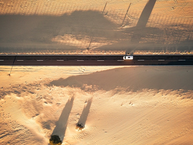 両側に砂と砂漠がある黒いまっすぐなアスファルト道路の航空写真-真ん中を走行する車-エキゾチックな砂漠の目的地のための放浪癖の概念-光と影