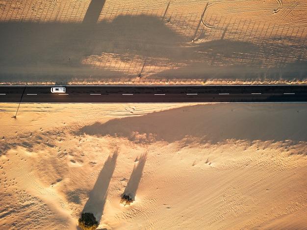 주위 양쪽에 모래와 사막이있는 검은 직선 아스팔트 도로의 공중보기-중간에 여행하는 자동차-이국적인 사막 목적지에 대한 방랑벽의 개념