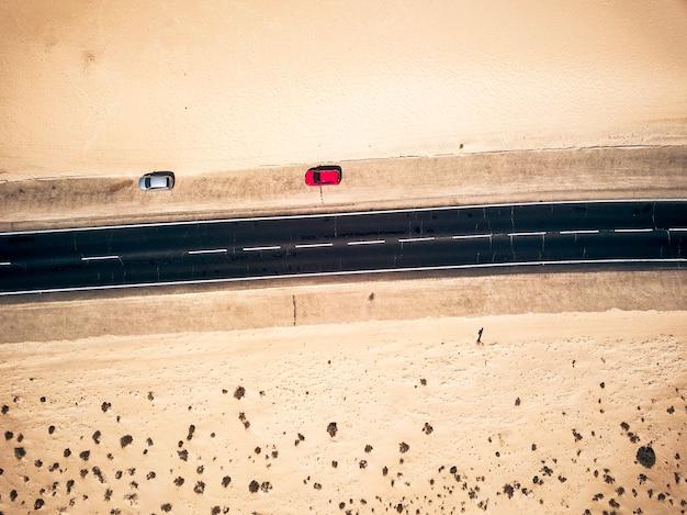 両側に砂と砂漠がある黒いまっすぐなアスファルト道路の航空写真-側面に2台の車が駐車されています-エキゾチックな目的地のための旅行と放浪癖の概念