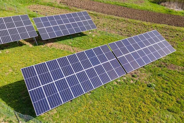 깨끗한 생태 전기를 생산하기 위해 뒤뜰 바닥에 장착된 파란색 광전지 태양 전지판의 공중 전망. 재생 에너지 개념의 생산입니다.