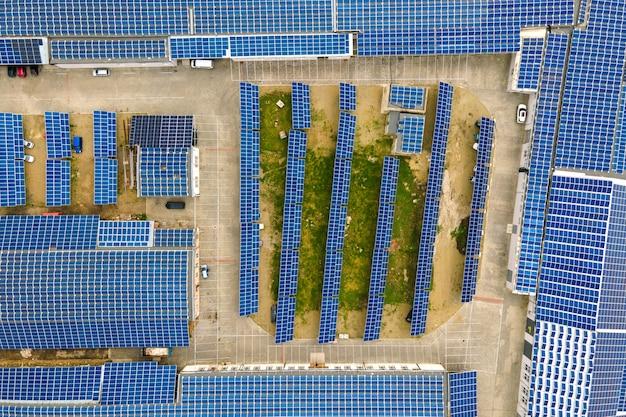 깨끗한 생태 전기를 생산하기 위해 산업 건물 지붕에 장착된 파란색 태양광 패널의 공중 전망. 재생 에너지 개념의 생산입니다.