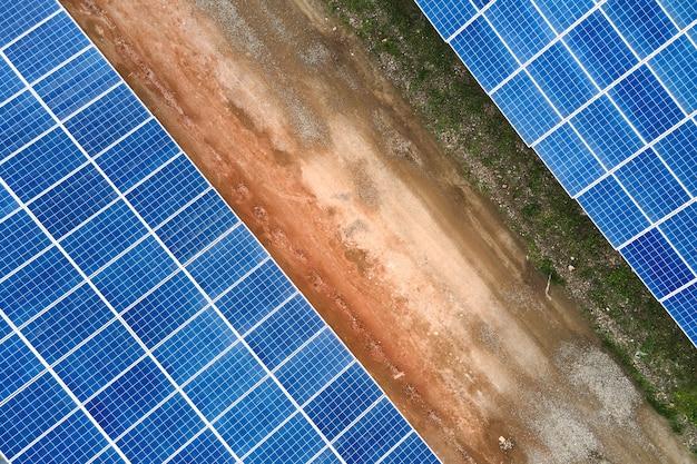 Вид с воздуха на голубые фотоэлектрические солнечные панели, установленные на крыше промышленного здания для производства экологически чистой электроэнергии. производство концепции устойчивой энергетики.