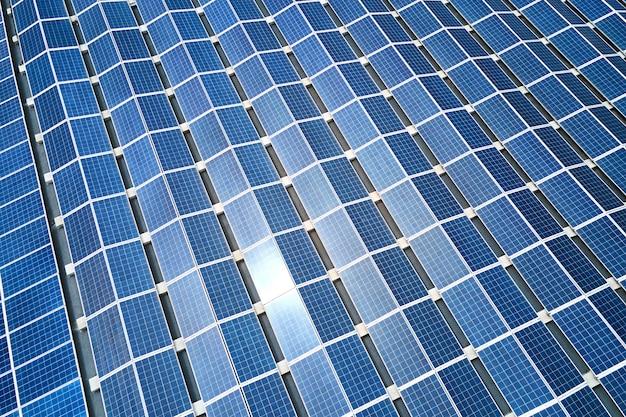 녹색 생태 전기를 생산하기 위해 산업 건물 지붕에 장착된 파란색 태양광 패널의 공중 전망. 지속 가능한 에너지 개념의 생산.