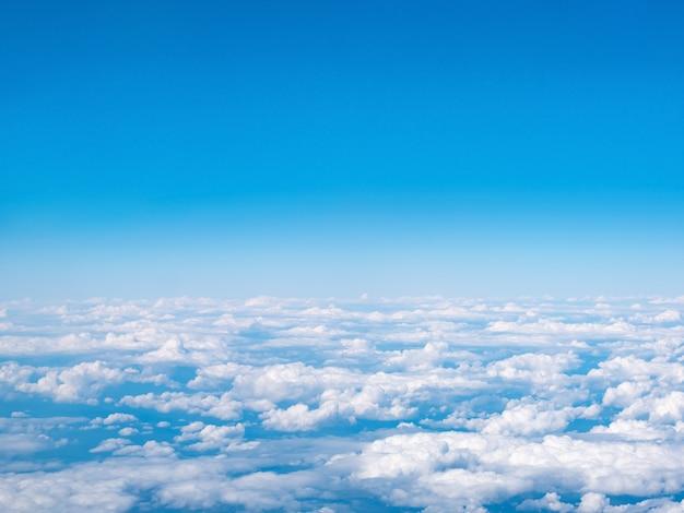Вид с воздуха на голубое небо и белые облака. вид сверху из окна самолета