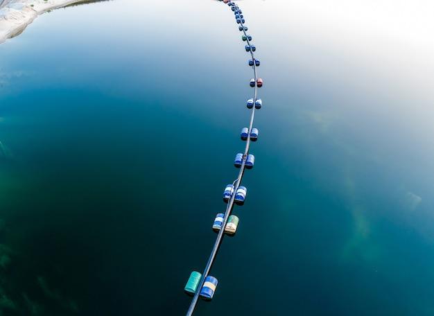 깊은 남색 호수에 배럴이 있는 파란색 튜브의 항공 보기