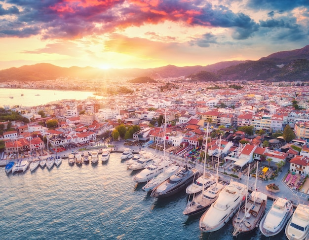 ボートやヨット、トルコのマルマリスの日没時の美しい街の空撮。ボート、青い海、色とりどりの空、家、山のある風景。ヨーロッパの港の平面図。旅行。都市の景観