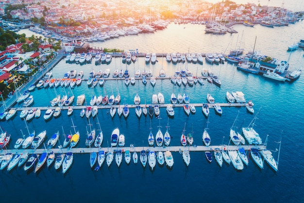 Вид с воздуха на лодки, парусники, яхты и красивую архитектуру на закате летом в мармарисе, турция.